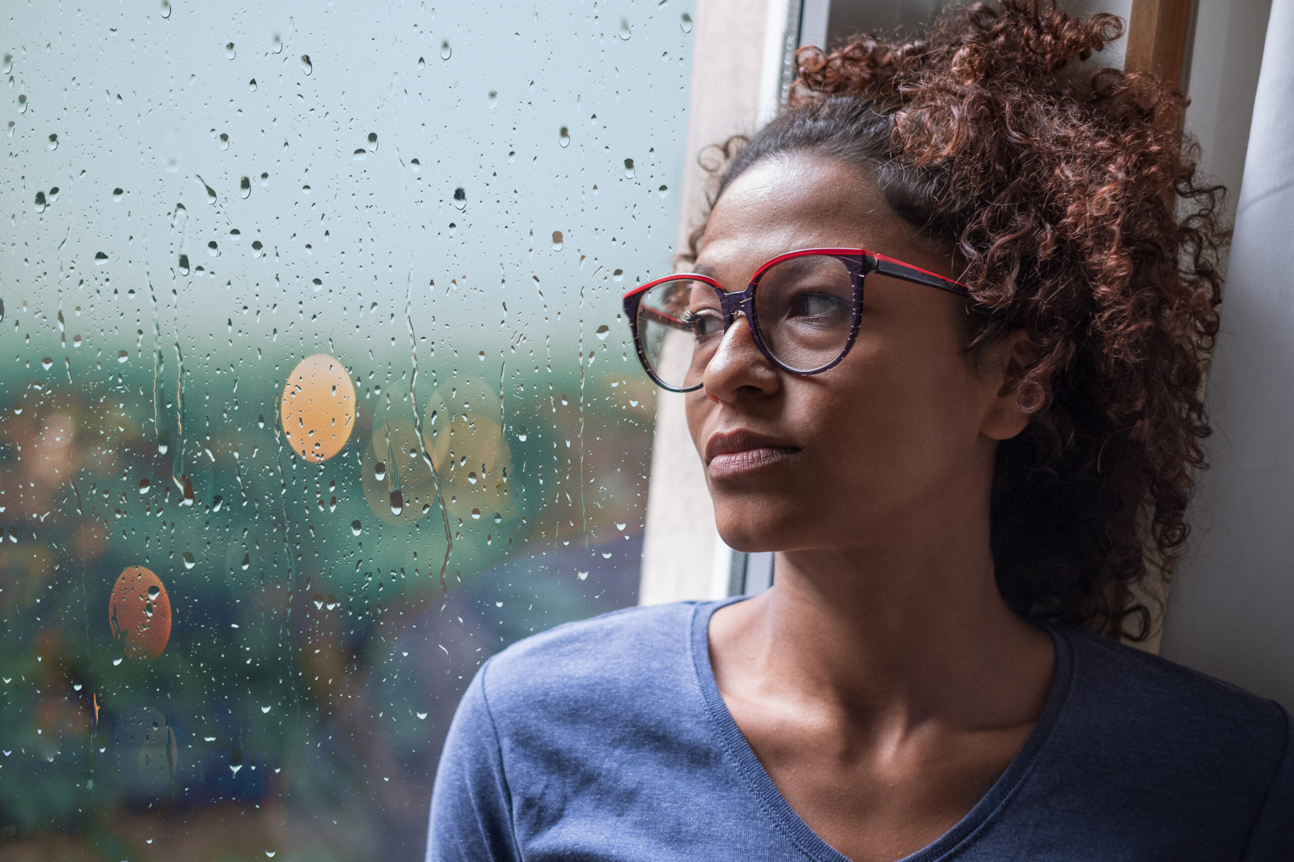 Woman looking out the window; managing stress and anxiety