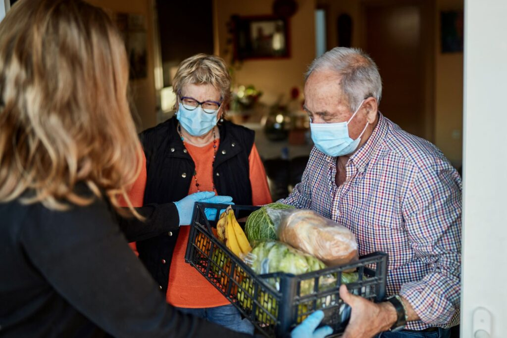 A lady helps the community by delivering food to older people who are self isolating