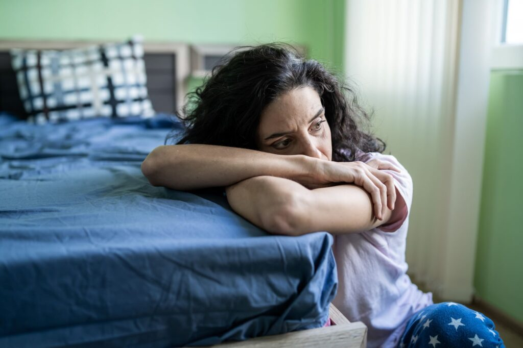 woman feeling tired sitting on the floor resting her head on the bed