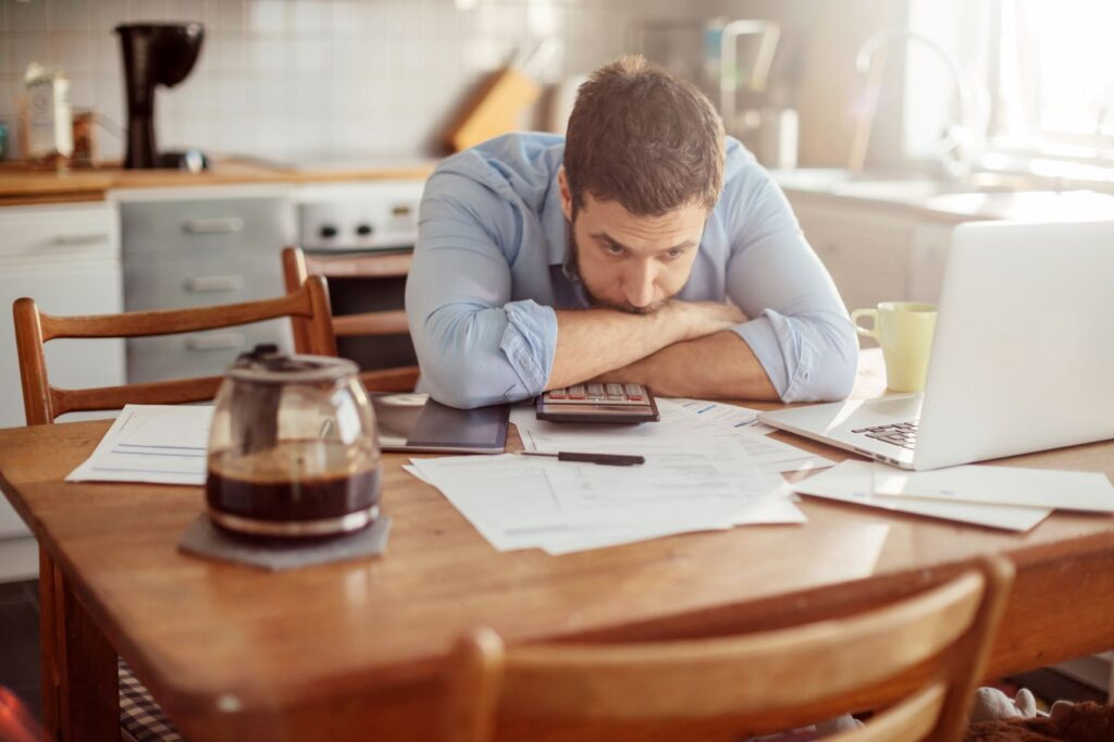 stressed man resting head on table with papers scattered in front of him