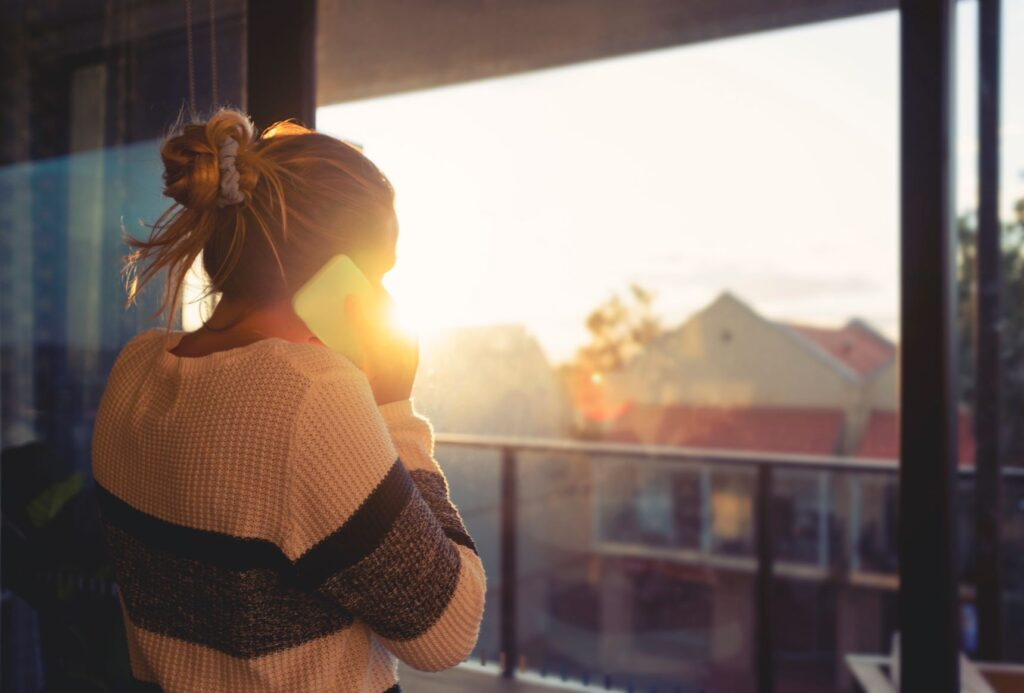 Talking Therapies: A woman talks on the phone looking out of her window at the sunny sky
